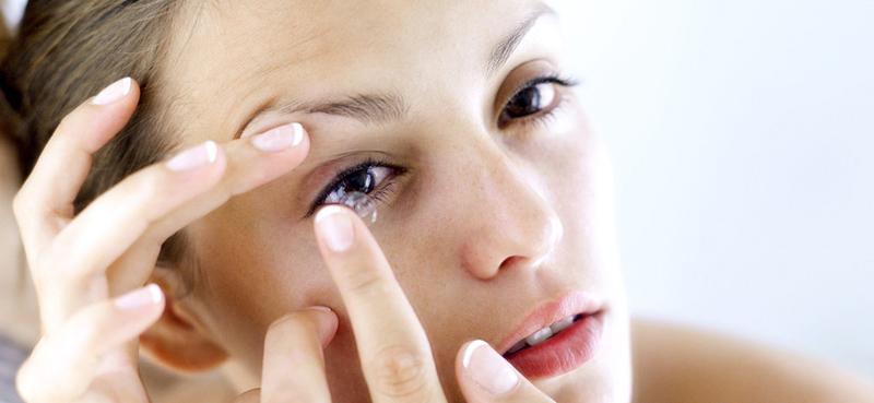 Mulher aplicando lentes de contactos aos olhos